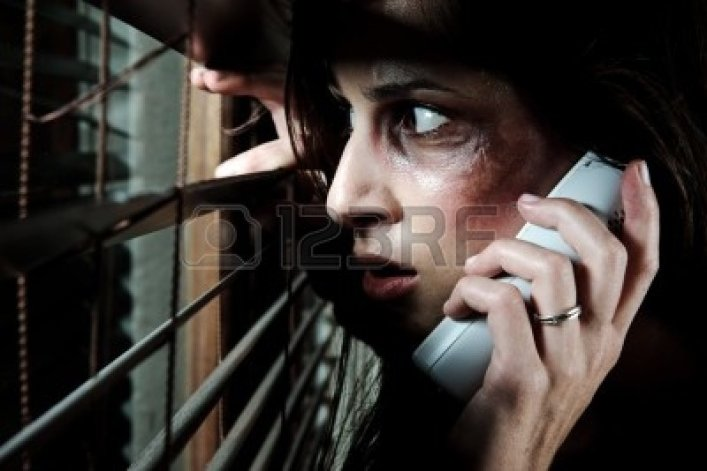 8726455-fearful-battered-woman-peeking-through-the-blinds-to-see-if-her-husband-is-home-while-calling-for-he