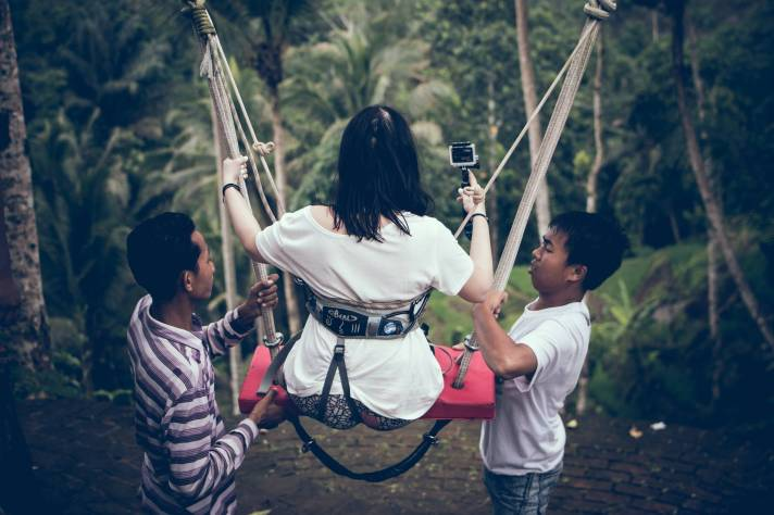 two men assisting woman riding on swing